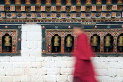 Bhutanese prayer wheels with young monk passing by